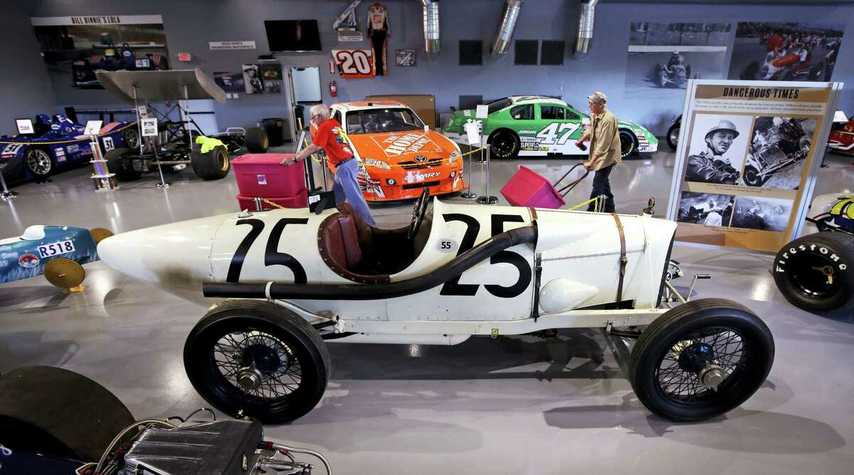 In this Wednesday, May 31, 2017 photograph, volunteers wheel supplies past a 1915 Duesenberg race car (#25), which raced in Boston, at the North East Motor Sports Museum in Loudon, N.H. The museum dedicated to motorsports in New England resides just outside the front gates the New Hampshire Motor Speedway. (AP Photo/Charles Krupa)