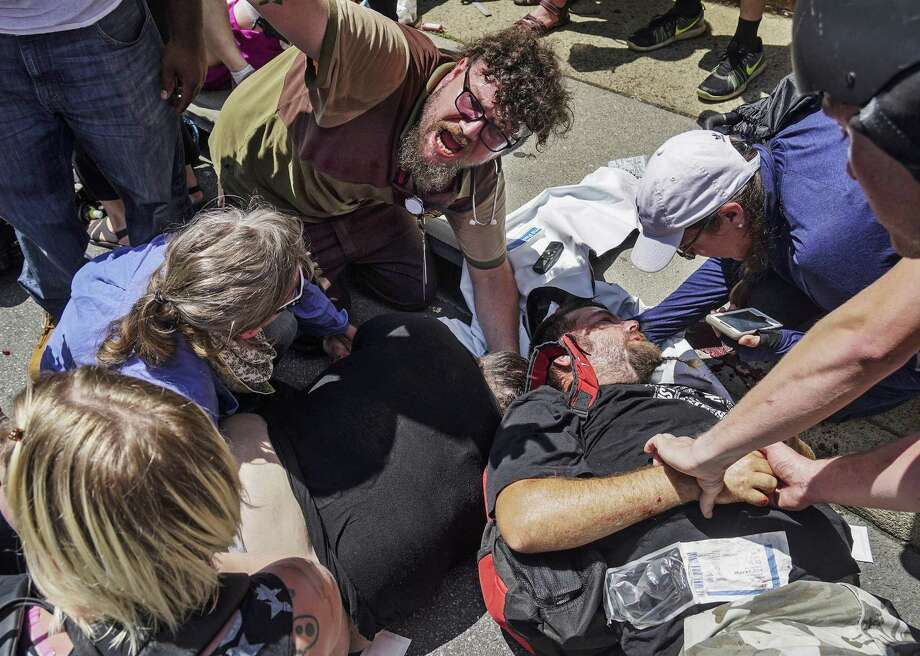 """Responders work Aug. 12 with victims at the scene where a man identified by police as James Alex Fields Jr., plowed a car into a crowd of people who had gathered to protest a white supremacist rally earlier in the day, in Charlottesville, Va. Laws in six states would protect drivers who """"unintentionally"""" hit protesters obstructing traffic — measures that will tip the calculus toward hitting protesters. Photo: Go Nakamura /Associated Press / Go Nakamura"""
