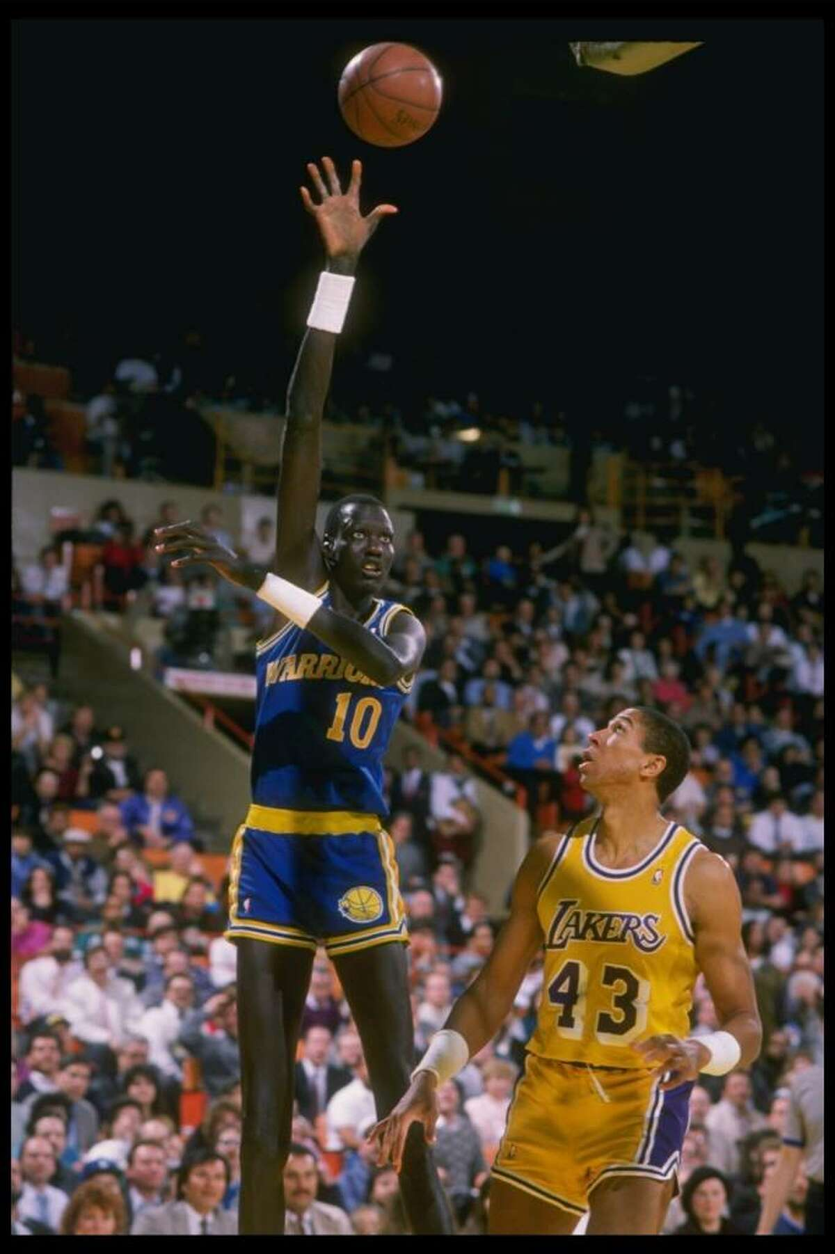 1988-1989: Center Manute Bol of the Golden State Warriors in action against Mychal Thompson of the Los Angeles Lakers (right) during a game at the Great Western Forum in Inglewood, California. Mandatory Credit: Allen Steele /Allsport