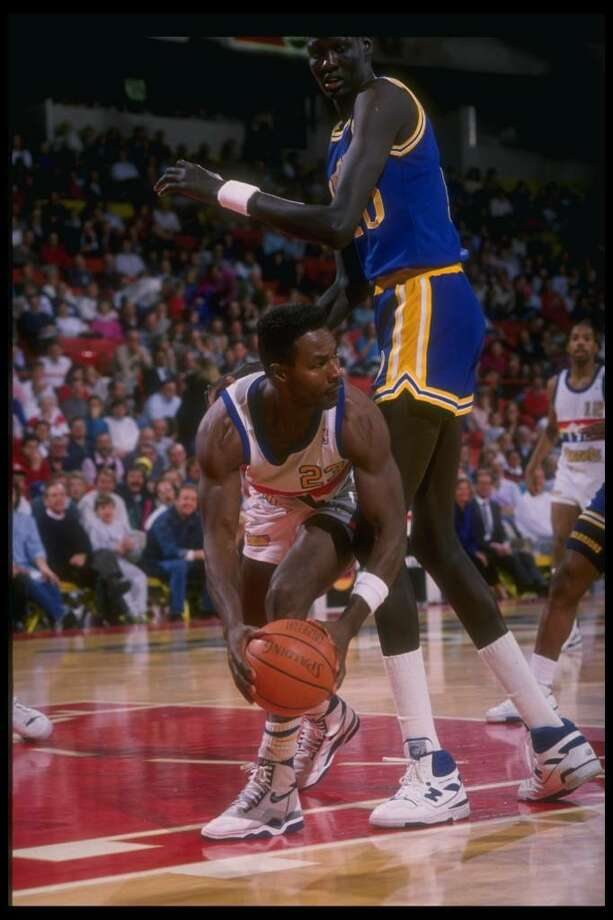 1989-1990:  T. R. Dunn of the Denver Nuggets looks to pass around center Manute Bol of the Golden State Warriors during a Nuggets game versus the Warriors at the McNichols Sports Arena in Denver, Colorado. Mandatory Credit: Tim DeFrisco  /Allsport Mandato Photo: Tim DeFrisco, Getty Images / Getty Images North America