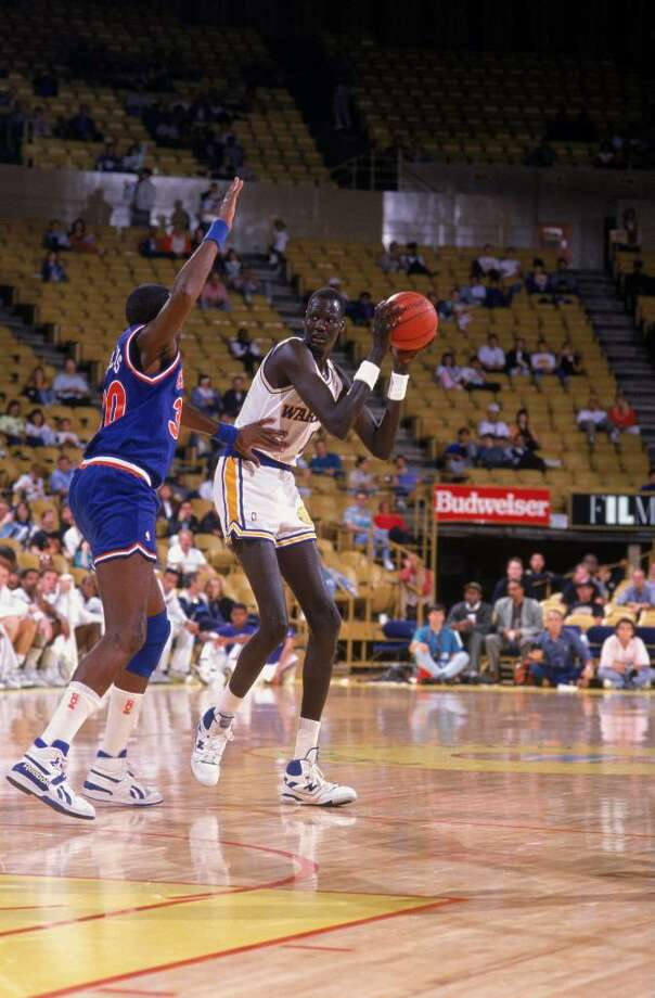 1989:  Manute Bol #11 of the Golden Sate Warriors looks to pass the ball during a game. NOTE TO USER: User expressly acknowledges and agrees that, by downloading and/or using this Photograph, User is consenting to the terms and conditions of the Getty Images License Agreement. Mandatory copyright notice: Copyright 2001 NBAE  Mandatory Credit: Ken Levine/Getty Images Photo: Ken Levine, Getty Images / Getty Images North America