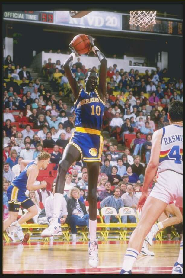 1989-1990:  Manute Bol of the Golden State Warriors in action with the basketball. Mandatory Credit: Tim de Frisco  /Allsport Photo: Tim Defrisco, Getty Images / Getty Images North America