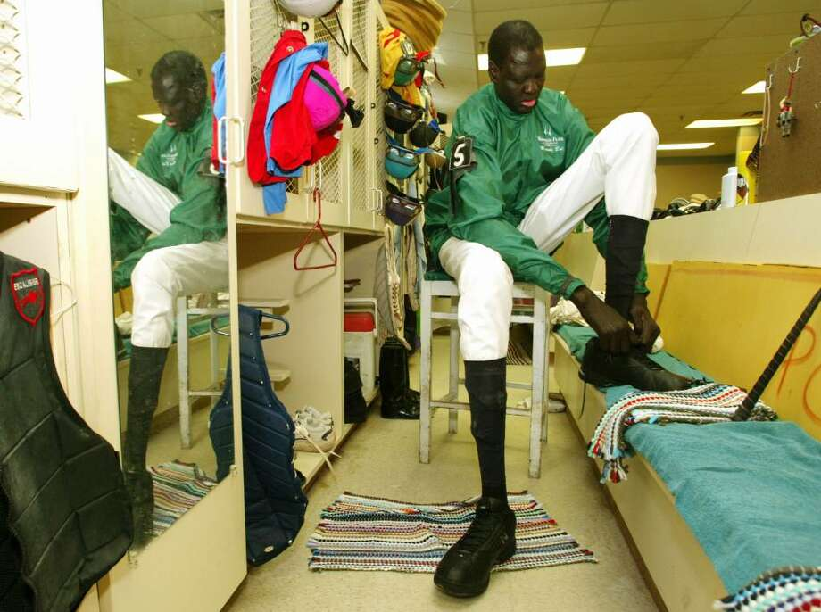 ANDERSON, IN - OCTOBER 18:  Former NBA star Manute Bol laces up his shoes while wearing riding silks in the jockey's room at Hoosier Park October 18, 2003 in Anderson, Indiana. Bol, who played 11 seasons in the NBA and was the tallest man in professional basketball at 7-foot-7, appeared at the thoroughbred racing track north of Indianapolis as part of a charity effort to raise money for refugees in his native Sudan. Bol became the tallest jockey ever licensed by the Indiana Horse Racing Commission.  (Photo by Brent Smith/Getty Images) Photo: Brent Smith, Getty Images / 2003 Getty Images