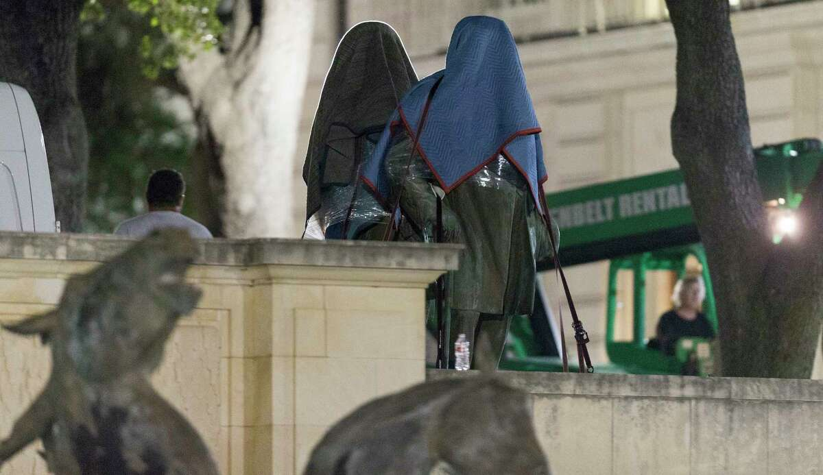 Statues of Texas Gov. James Stephen Hogg and Confederate Postmaster General John H. Reagan are removed from the south mall of the University of Texas at Austin early Monday. (Stephen Spillman)