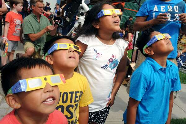 From left, brothers Johan and Justin Verano and their cousins Yozlie and Emely Hernandaz, all of Bridgeport, view the solar eclipse at the Discovery Museum in Bridgeport, Conn. Aug. 21, 2017.