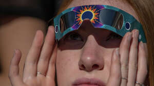 Spectators watch the 2017 solar eclipse through special glasses, at the Pacific Science Center in Seattle on Monday, Aug. 21, 2017.