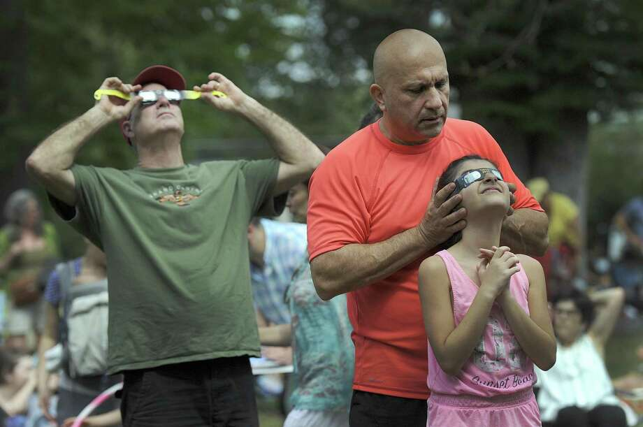 Eli Shartouni, right, holds filtered glasses over daughter Natalie's eyes so she can safely view Monday's eclipse. Left is David Sarath. The Ridgefield residents were at Ballard Park in Ridgefield Monday watiching the eclipse with hundreds of others. Photo: Carol Kaliff / Hearst Connecticut Media / The News-Times
