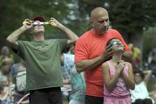 Eli Shartouni, right, holds filtered glasses over daughter Natalie's eyes so she can safely view Monday's eclipse. Left is David Sarath. The Ridgefield residents were at Ballard Park in Ridgefield Monday watiching the eclipse with hundreds of others.