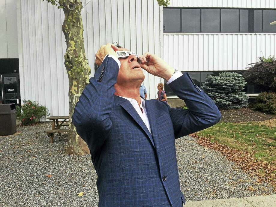 Connecticut Gov. Dannel Malloy uses special glasses to look at the solar eclipse Monday outside the New Haven Register building in New Haven. Photo: Viktoria Sundqvist / Hearst Connecticut Media