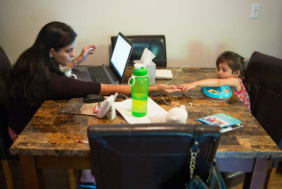 H-4 visa holder Karishma Chawla works on her laptop at home in San Jose while her daughter, Naisha, shares her snack. Photo: James Tensuan, Special To The Chronicle