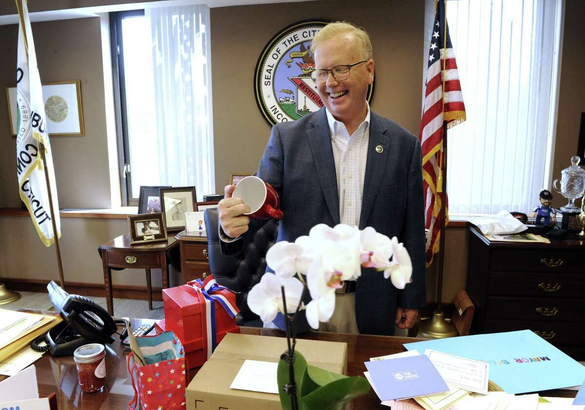 """Mayor Mark Boughton returns to work at City Hall Monday, August 21, 2017, after undergoing brain surgery. He arrives to find his office filled with cards and gifts, including the cup he is looking at that reads """"Get well and make CT great again."""""""