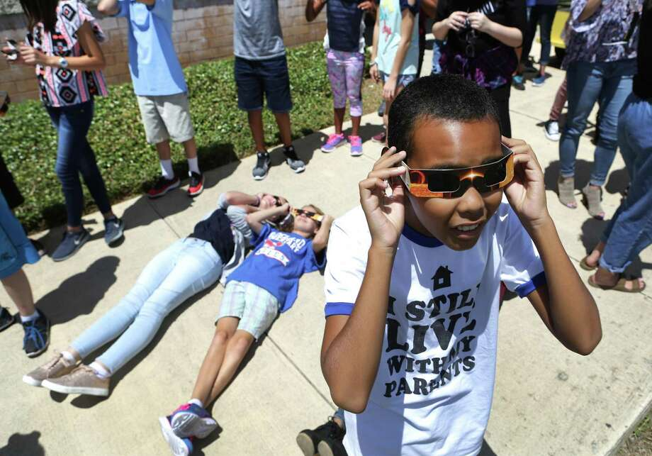 Kevin Brown, right, adjusts his special solar glasses as teachers and students at Virginia Allred Stacey Junior-Senior High School at Lackland AFB, witness the eclipse. Photo: Bob Owen /San Antonio Express-News / ©2017 San Antonio Express-News