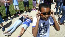 Kevin Brown, right, adjusts his special solar glasses as teachers and students at Virginia Allred Stacey Junior-Senior High School at Lackland AFB, witness the eclipse.