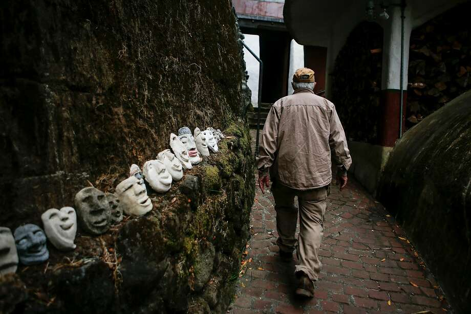 David Lee Hoffman walks past a collection of masks on his property. Photo: Nicole Boliaux, The Chronicle