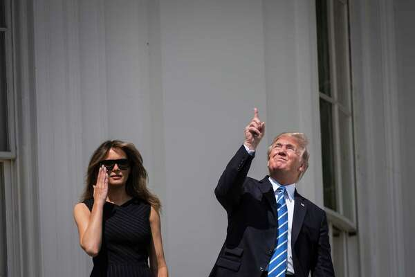 President Donald Trump looks up toward the solar eclipse, with first lady Melania Trump by his side, from a balcony at the White House.