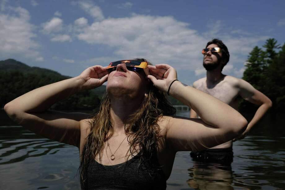 Norwalk Hour reporter Kaitlyn Krasselt drove to North Carolina to see the total solar eclipse on Monday. Erik Nelson of Enfield, Connecticut, is behind her. Photo: Philip Vukelich / Hearst Connecticut Media / Connecticut Post