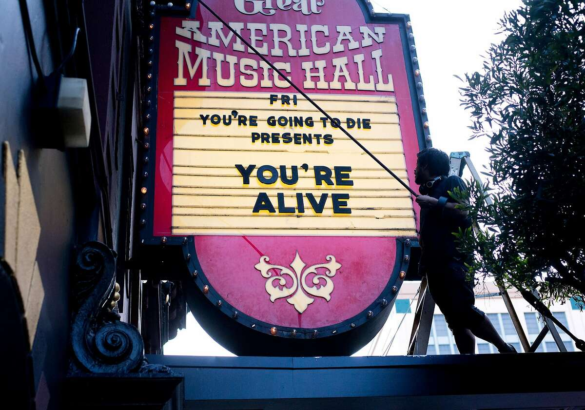 A worker changes the Great American Music Hall's marquee before You're Alive, an event staged by You're Going to Die, on Friday, Aug. 11, 2017, in San Francisco.