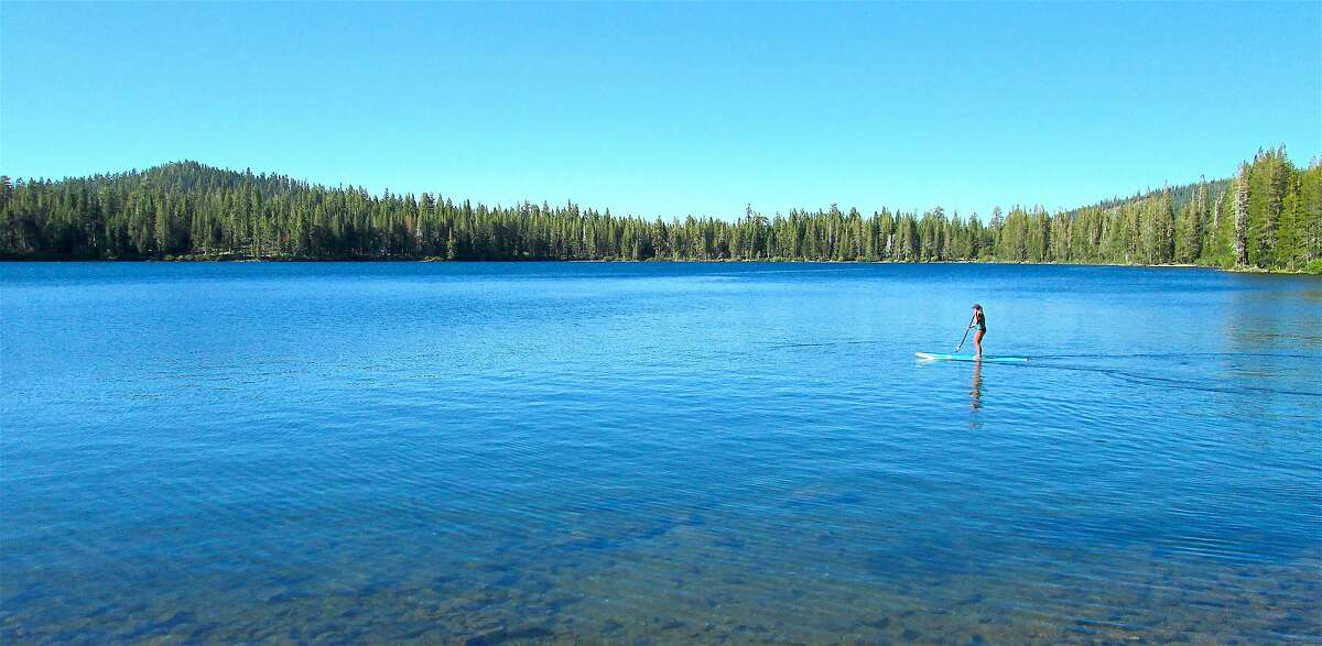 A lone paddler on an SUP cruises the calm waters on the eastern end of Gold Lake in the Lakes Basin Recreation Area in Plumas National Forest