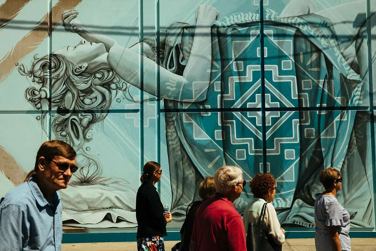 A group tour walks past Miles Toland's mural on 730 R Street in Sacramento.