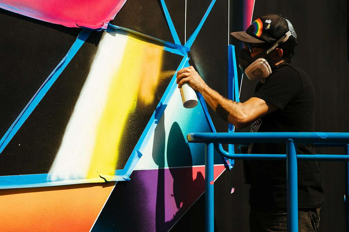 """Jose Di Gregorio works on his mural, """"Total Eclipse of the Heart."""""""