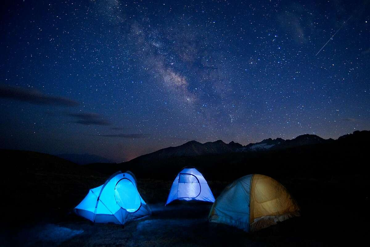 Tents set up near the Palisades in the high Sierra Nevada below the Milky Way and a spectacular night sky, captured in a time-lapse photograph