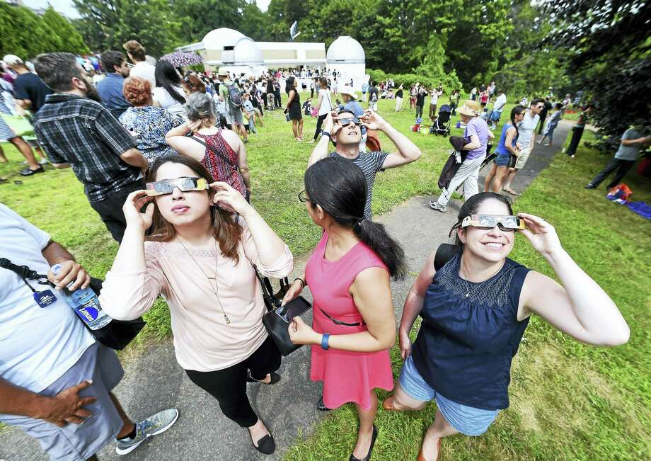 Left to right, Fauzia Riaz, Todd Olszewski and Deborah Doroshon watch the solar eclipse with eclipse glasses as they wait in line to enter Yale University's Leitner Family Observatory and Planetarium in New Haven on 8/21/2017.  Arnold Gold / Hearst Connecticut Media Photo: Arnold Gold / Hearst Connecticut Media / New Haven Register