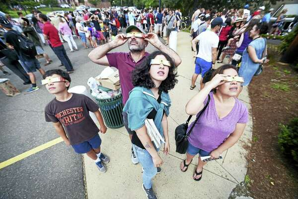 From left, Eli Kleinman, 12; his father, Ben; sister, Ava, 14; and mother, Tammy, of Hamden watch the solar eclipse with eclipse glasses as they wait in line to enter Yale University's Leitner Family Observatory and Planetarium in New Haven Monday.
