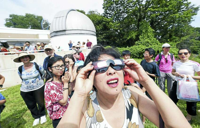 Linda Li of Hamden looks through eclipse glasses as the solar eclipse begins on the grounds of Yale University's Leitner Family Observatory and Planetarium in New Haven on 8/21/2017. Arnold Gold / Hearst Connecticut Media