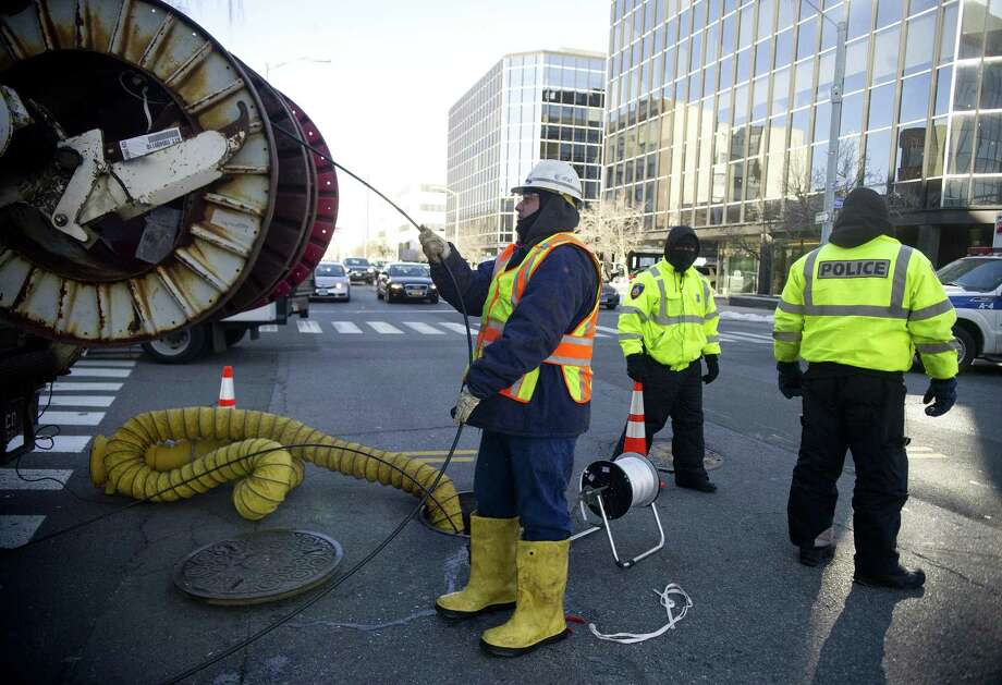 File photo - An AT&T employee, left, installs a fiber optic cable as police officers control traffic in Stamford, Conn., on January 7, 2014. AT&T said Tuesday its fiber network is now available in new areas of San Antonio, parts of Alamo Heights and Castle Hills. Photo: Lindsay Perry /Lindsay Perry / Stamford Advocate