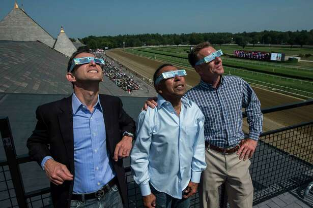 Three Eclipse Award winning jockeys from left are Ramon Dominguez, Angel Cordero Jr. and Richard Migliore as they watch the partial eclipse of the sun from the roof of the Saratoga Race Course Monday Aug. 21, 2017 in Saratoga Springs, N.Y.  (Skip Dickstein/Times Union)