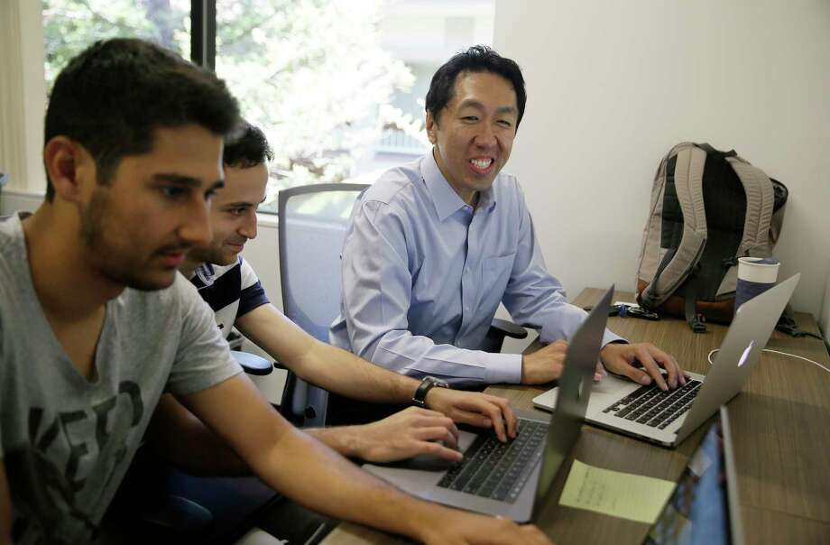 Computer scientist Andrew Ng, right, works with others at his office in Palo Alto, Calif. Ng, one of the top researchers in machine learning and artificial intelligence, is building new ways to help educate the next generation of AI specialists. Photo: Eric Risberg, STF / Copyright 2017 The Associated Press. All rights reserved.
