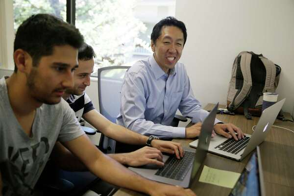 Computer scientist Andrew Ng, right, works with others at his office in Palo Alto, Calif. Ng, one of the top researchers in machine learning and artificial intelligence, is building new ways to help educate the next generation of AI specialists.