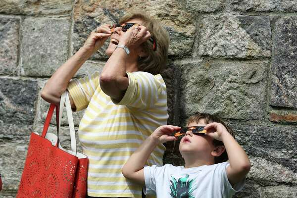 Stamford residents Chryl Axelrod and her grandson Shane Axelrod, 5, look up to see the partial eclipse at the Stamford Museum and Nature Center in Stamford, Conn. on Monday, August 21, 2017.