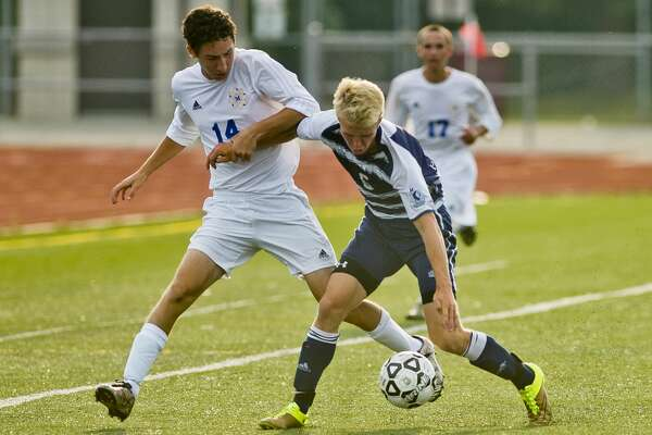 Midland's Mason Pilgrim, left, fights for possession with Petoskey's Drew Block during their game on Monday, August 21, 2017 in Midland.