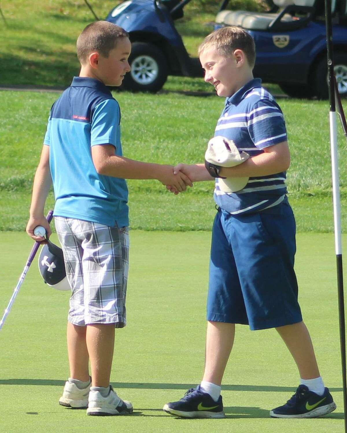 Max Pawlowski, left, andAidan Henn share a congratulatory handshake after finishing up on the 18th green at the Fran McCarthy Junior Golf Tournament at Richter Park Golf Course in Danbury Aug. 21, 2017.