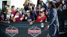 Houston Texans defensive end Jadeveon Clowney, right, slaps hands with fans as he walks to practice during training camp at The Methodist Training Center on Monday, Aug. 21, 2017, in Houston. ( Brett Coomer / Houston Chronicle )