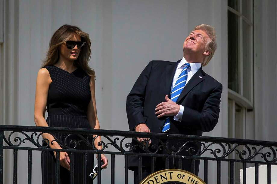 President Donald Trump and first lady Melania Trump view the solar eclipse from the Truman balcony of the White House, in Washington on Monday. Photo: AL DRAGO, STR / NYTNS