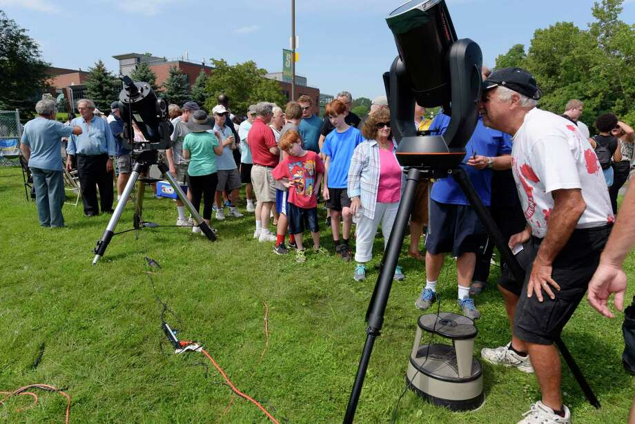 People gather around a telescope as they wait their turn to view the solar eclipse on the campus of Siena College on Monday, Aug. 21, 2017, in Loudonville, N.Y.      (Paul Buckowski / Times Union) Photo: PAUL BUCKOWSKI / 20041264A