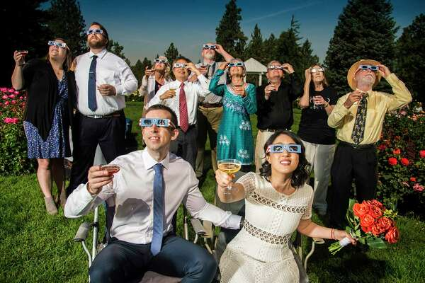 After their wedding ceremony, groom and bride, Nathan Mauger, Connie Young with family and friends, toast to the solar eclipse from the Rose Garden in Manito Park in Spokane, Wash.