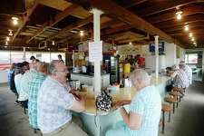 Don Murphy of Midland, left, and Nancy Pahl of Hemlock, right, catch up after running into each other last week for the first time in at least 50 years at the Studley Grange concession stand at the Midland County Fairgrounds. (Katy Kildee/kkildee@mdn.net)