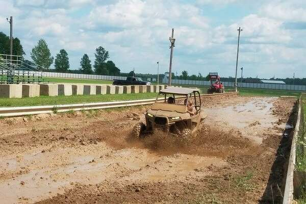 Driver Hunter Michalik and his passenger, cousin Meteo Booth, both of Flint, take a second dip in the mud course Saturday during the Gladwin County ORV Fun Fest. This is Michalik's third time attending the event and Booth's first ride. (Tereasa Nims/for the Daily News)