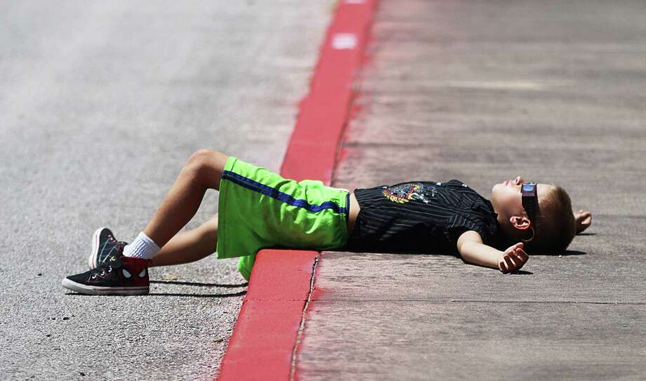 Keith Vollert of Liberty lies across the sidewalk at Liberty Middle School relaxing as he watches the solar eclipse. The Liberty Elementary School student arrived early and stayed late taking in every minute of the astronomical event. Photo: David Taylor