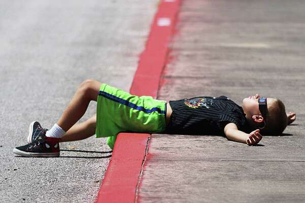 Keith Vollert of Liberty lies across the sidewalk at Liberty Middle School relaxing as he watches the solar eclipse. The Liberty Elementary School student arrived early and stayed late taking in every minute of the astronomical event.