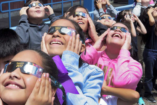 Santa Maria Elementary students wear their protective glasses as they follow the partial solar eclipse outside their campus on Monday.