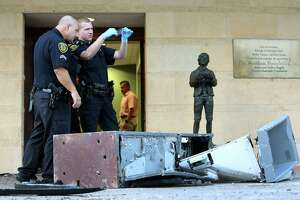 Houston Police Cpl. Dennis Eckenrode, left, and officer Kyle Nash look for fingerprints on an ATM machine that was pulled out by suspects using an SUV from the Miller Outdoor Theatre Tuesday, Aug. 22, 2017, in Houston.