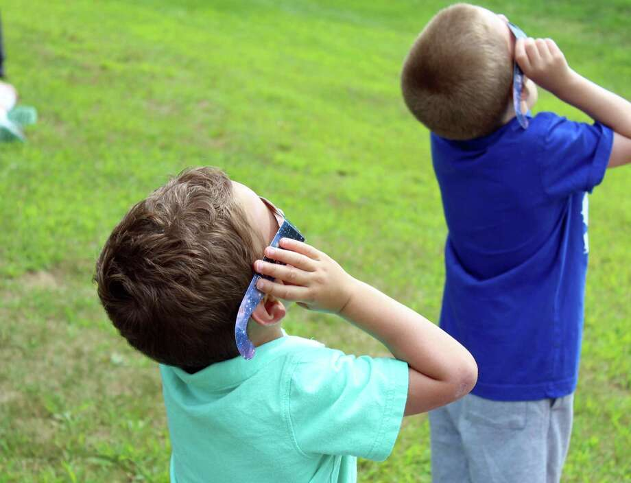 Sean, left, and Matthew Peregolise use special viewing glasses to safely look at Monday's partial solar eclipse. Fairfield,CT. 8/21/17 Photo: Genevieve Reilly / Hearst Connecticut Media / Fairfield Citizen