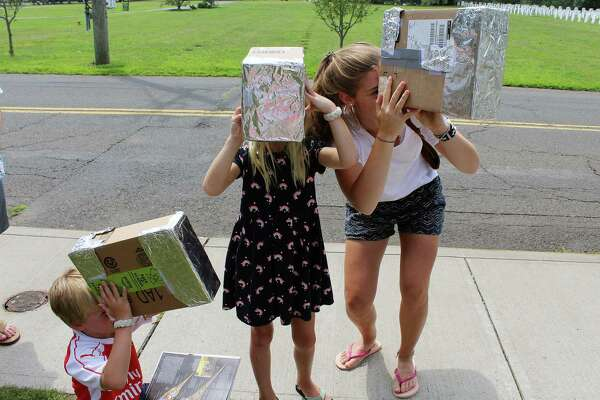 Alex (left), Emma and Amina Durbem practice with their homemade eclipse glasses at the Darien Library in Darien, Conn. on Aug. 21, 2017.