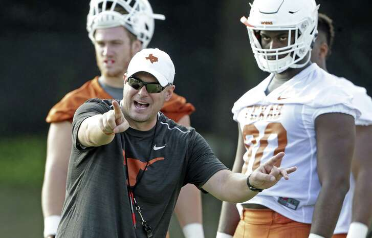 Coach Tom Herman spends time with UT linemen during fall drills on July 31.