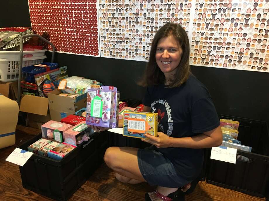 Elizabeth Fairfield coordinates the sorts packages from the Christmas in July drive of Lunches for Love to prepare for the annual Christmas program. Santa is expected to deliver about 600 gifts this season. Photo: Karen Zurawski