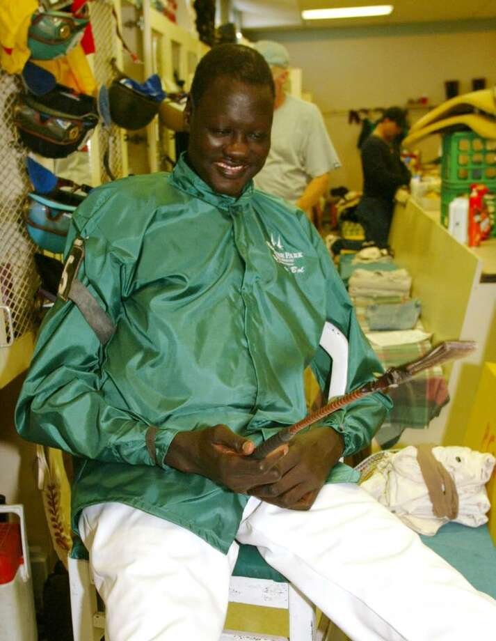 ANDERSON, IN - OCTOBER 18:  Former NBA star Manute Bol checks out a riding crop while wearing his silks in the jockey's room at Hoosier Park October 18, 2003 in Anderson, Indiana. Bol, who played 11 seasons in the NBA and was the tallest man in professional basketball at 7-foot-7, appeared at the thoroughbred racing track north of Indianapolis as part of a charity effort to raise money for refugees in his native Sudan. Bol became the tallest jockey ever licensed by the Indiana Horse Racing Commission.  (Photo by Brent Smith/Getty Images) Photo: Brent Smith, Getty Images / 2003 Getty Images